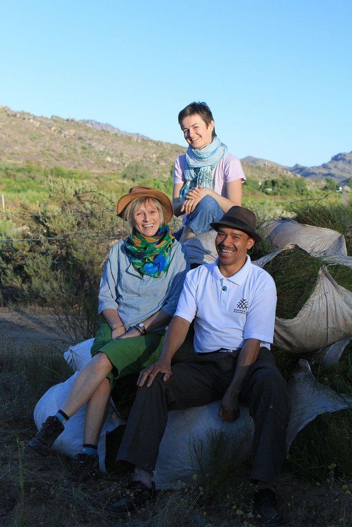 Arlette (fondatrice des Jardins de Gaïa à G.), Aurélie (responsable export) et Barend (responsable de la coopérative) posent avec les premiers ballots de rooibos. La saison s'annonce excellente !