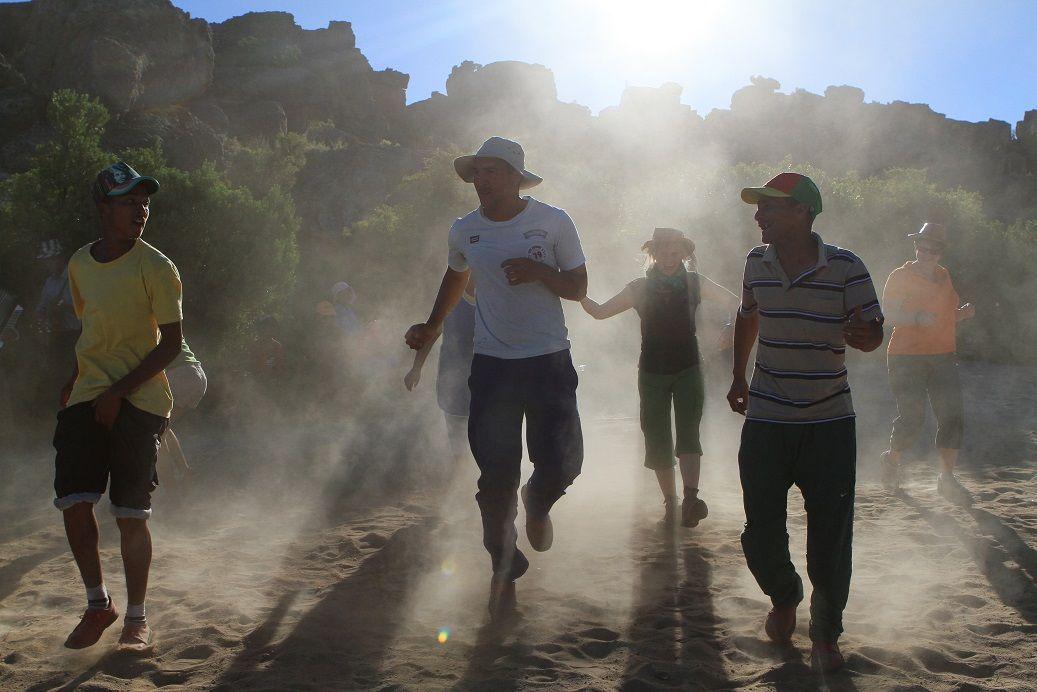 La journée se termine et nous reprenons la route. Au détour de la piste, un nuage de poussière et de sable s'élève : un groupe de danseurs khoisan est en pleine répétition. La tentation est trop grande et nous nous joignons au groupe !